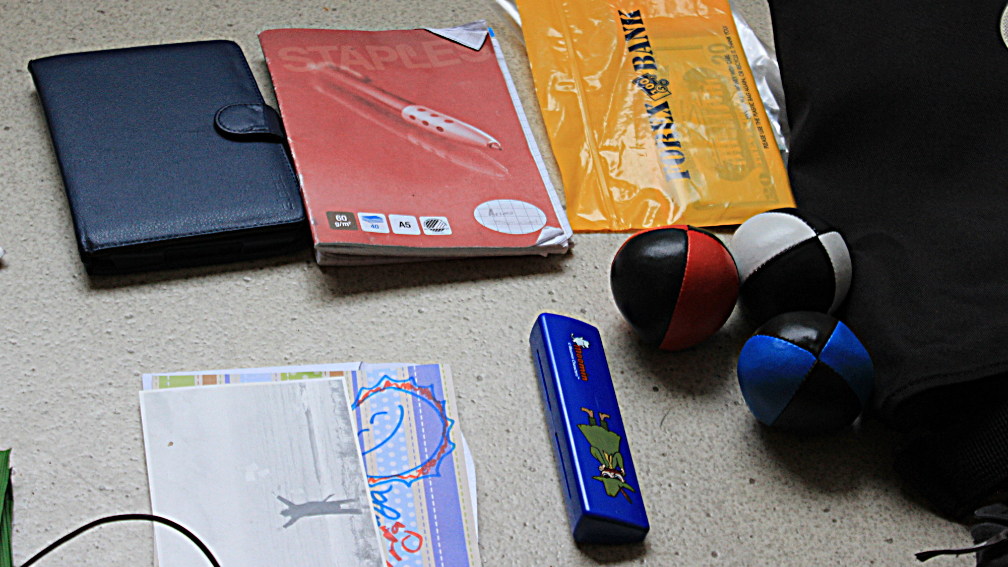 A harmonica, three juggling balls, an Amazon Kindle Paperwhite and a notebook.