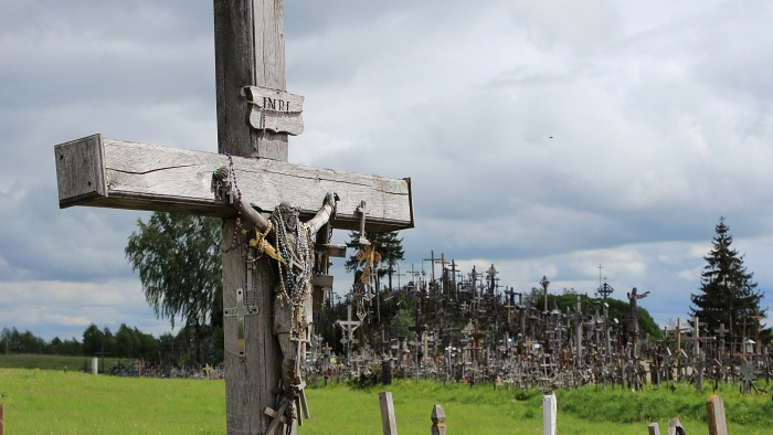 The Hill of Crosses, Šiauliai, Lithuania. A wooden crucifix with the Hill of Crosses in the background.