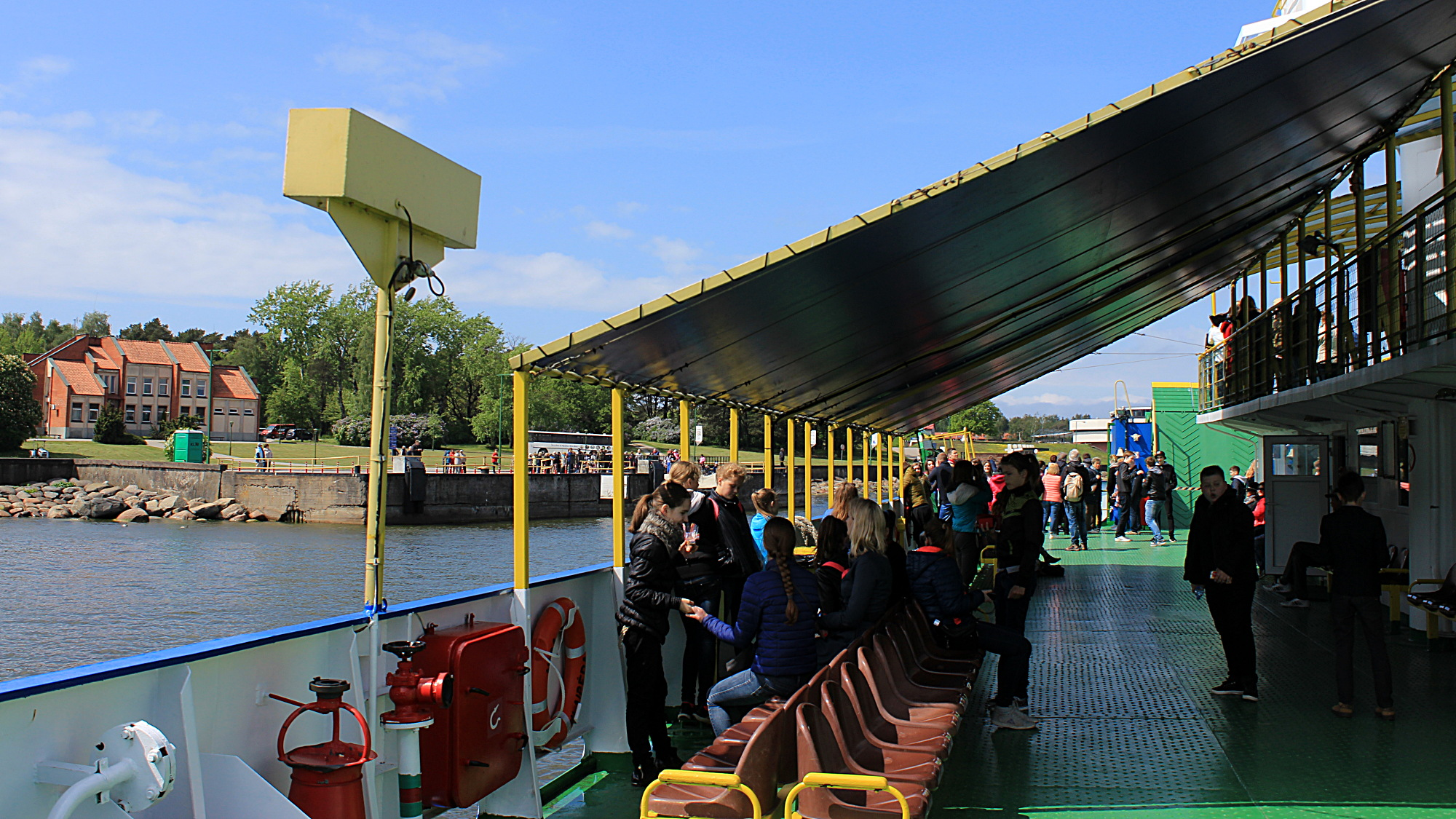 Schoolchildren on the deck of the ferry, looking at the sea and the landing area in Curonian Spit.