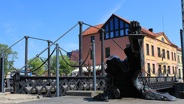 A hooded ghost statue rising from the sea with a lantern in Klaipeda, Lithuania.