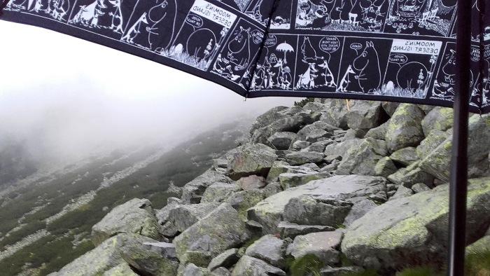 A black and white Moomin comic umbrella on a rocky mountain path.