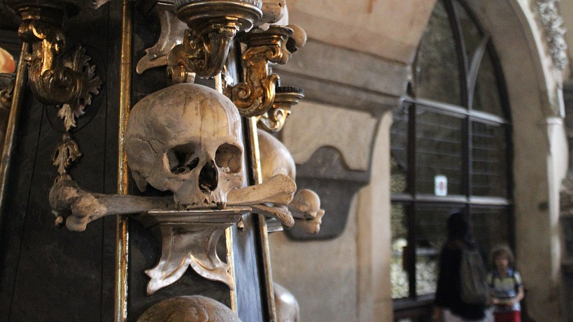 Sedlec Ossuary or Skull Church in Kutná Hora with a skull decoration in front.