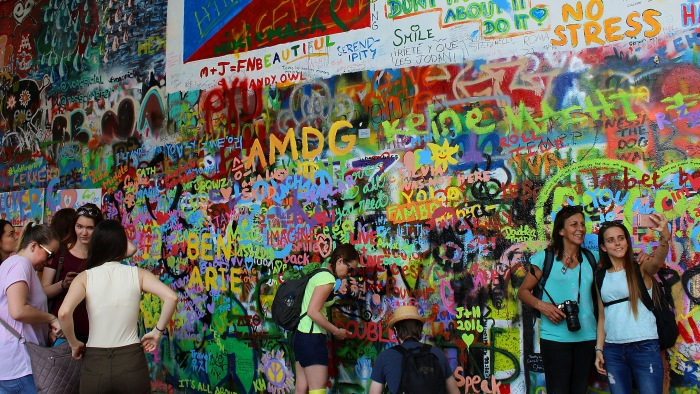 Colorful John Lennon wall of Prague in summer 2016 with tourists in front.