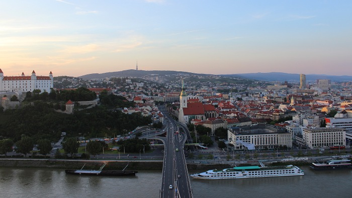 View from UFO Outlook tower over the bridge to the Old Town and Bratislava castle during sunset.