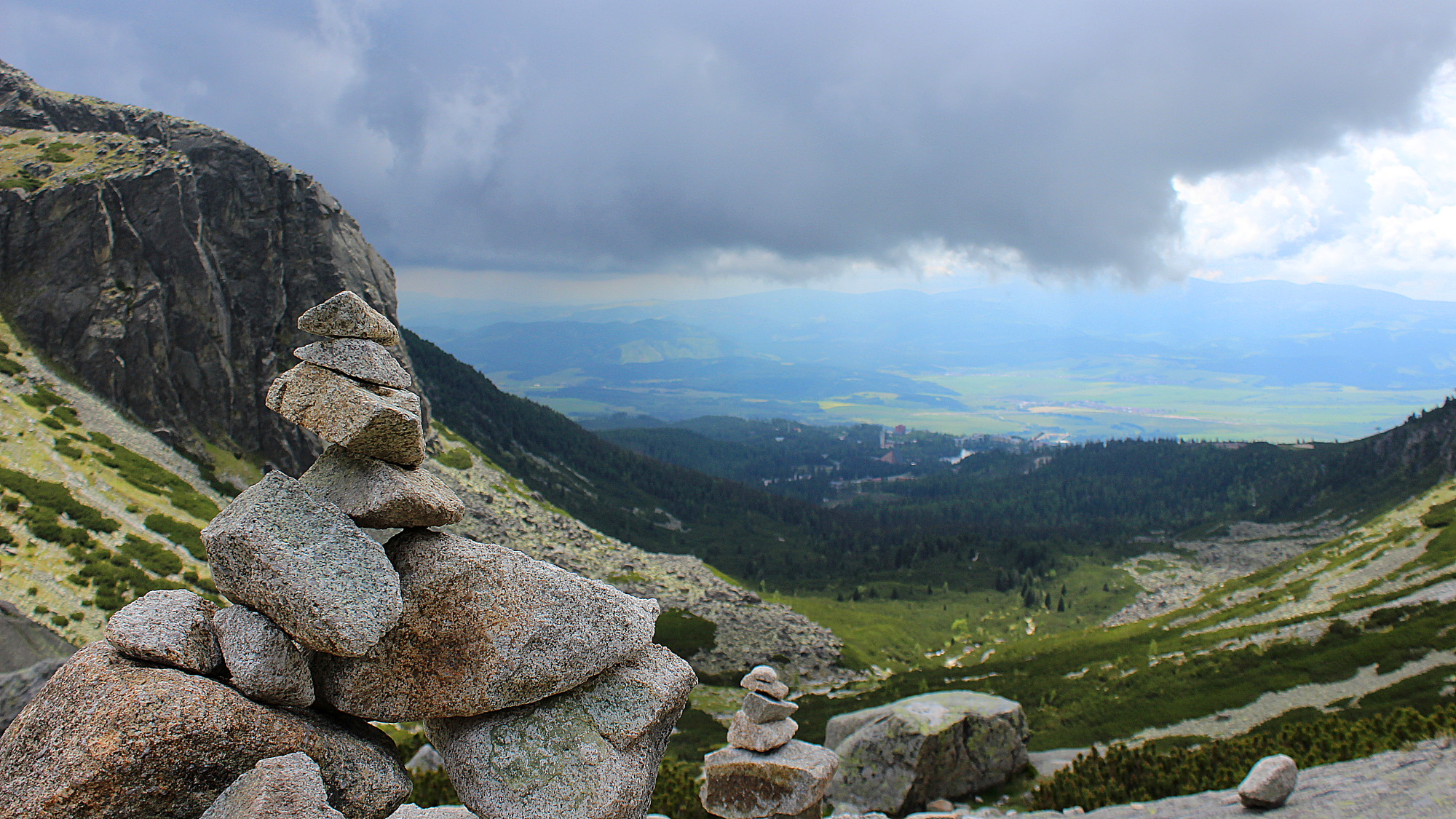 A pile of stones on a mountain in the High Tatras with a view down to the valley.