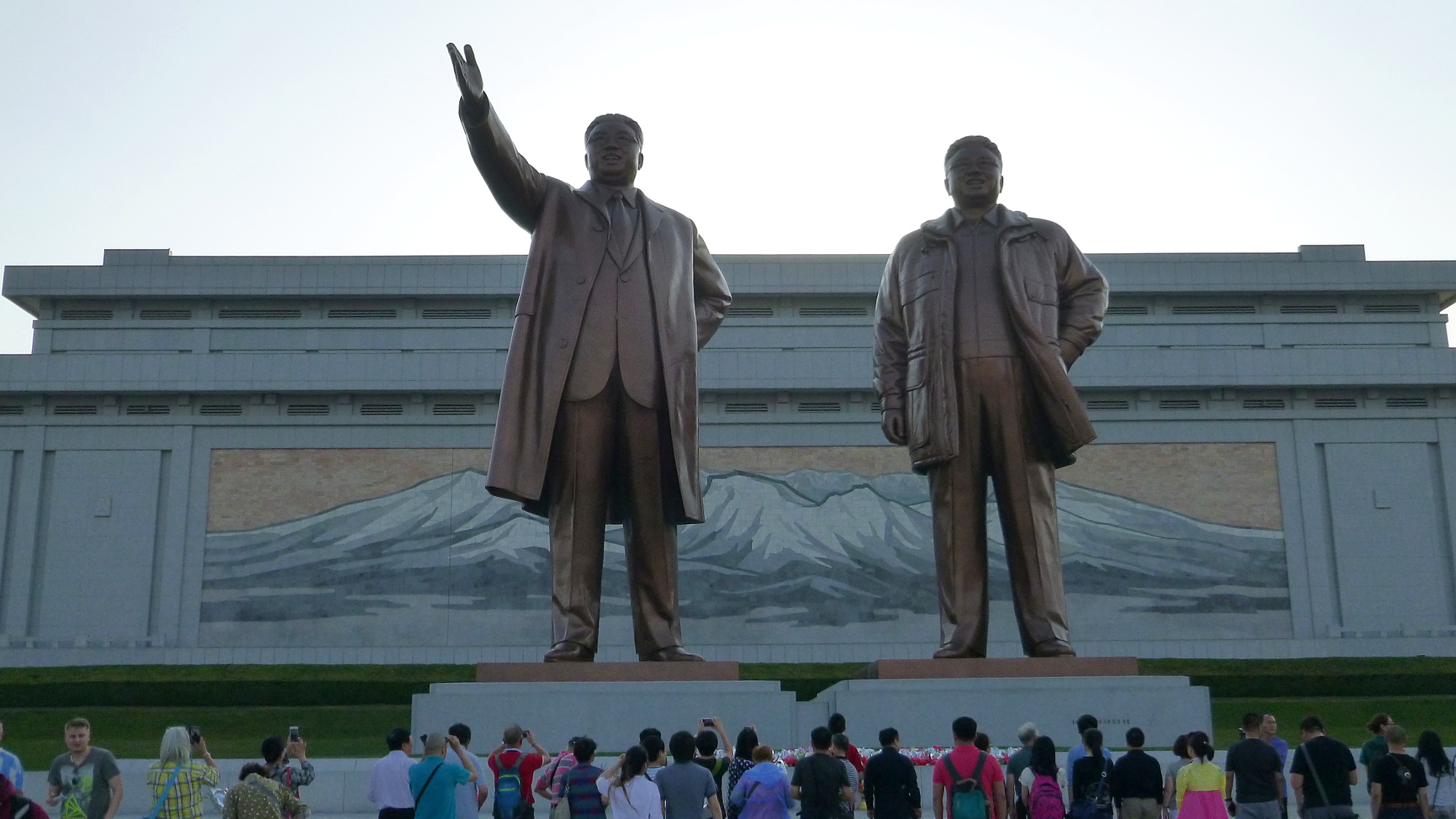 What is it like to visit North Korea? The famous bronze statues of North Korean leaders Kim Il-Sung and Kim Jong-Il with tourists in front.