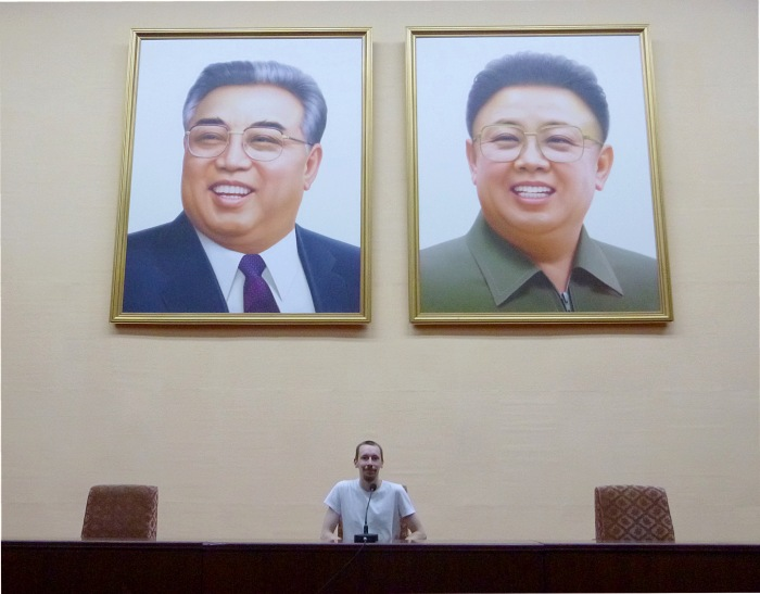 A tourist posing in a a lecture hall of Grand People's Study House in front of the pictures of Kim Il-Sung and Kim Jong-Un in Pyongyang, North Korea.