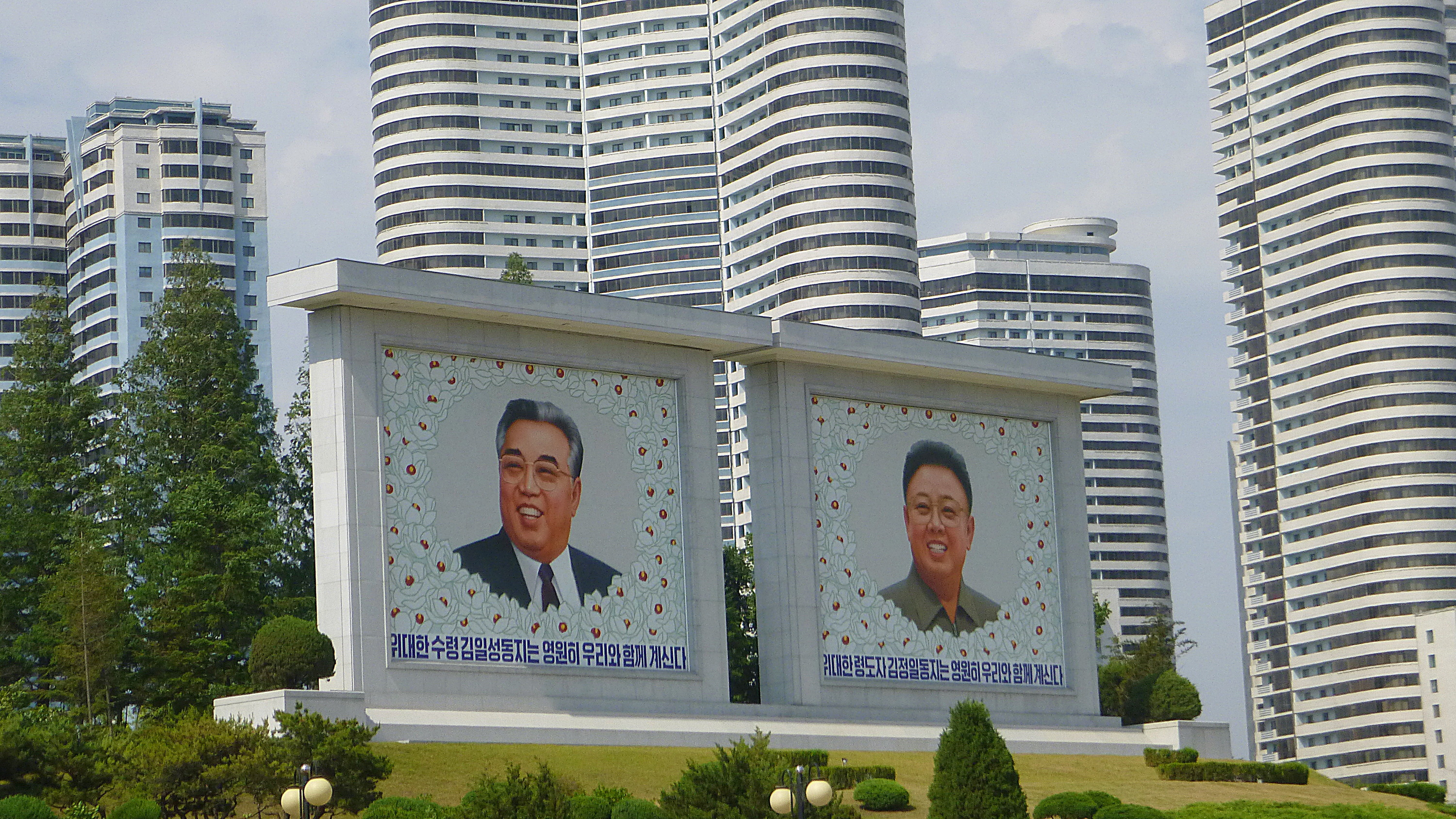 North Korea travel tips. Billboards of Kim Il-Sung and Kim Jong-Il with flowers in a park in Pyongyang.
